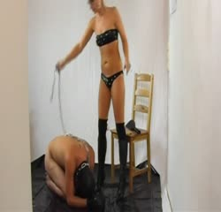 Black leather mistress plays with slave